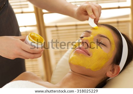 Close-up of young woman having facial mask in beauty parlor - stock photo