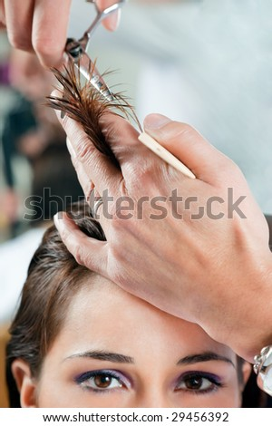 Close up of young woman having her hair being cut. Narrow focus on hand and hair