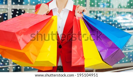 Close-up of  young woman holding colorful shopping bags - stock photo