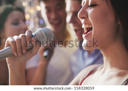 Close-up of young woman holding microphone and singing at karaoke - stock photo