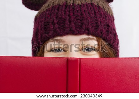 Close up of young woman holding red  book or diary wearing a winter hat looking like a head bear isolated on white background. - stock photo