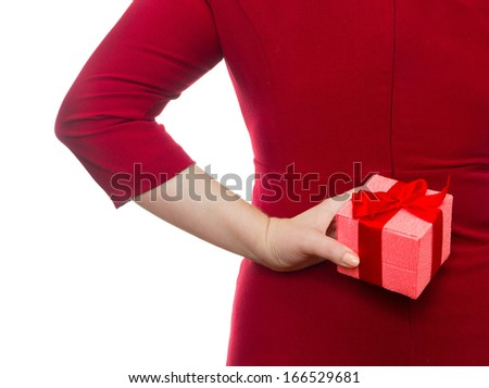 Close-up of young woman in red dress hiding behind her back the  - stock photo