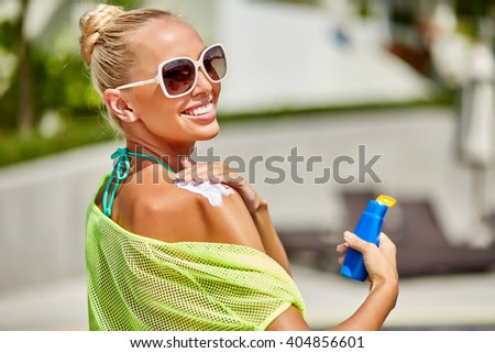 Close up of young woman in sunglasses putting sun cream on shoulder - stock photo