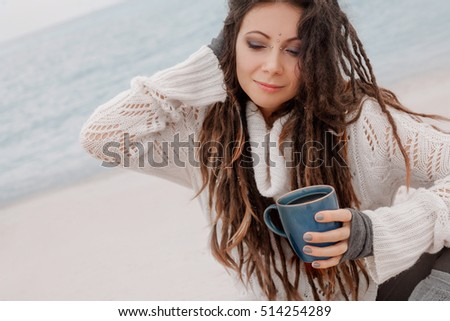 close up of young woman in sweater sitting on beach, holding cup of coffee in her hands with gloves