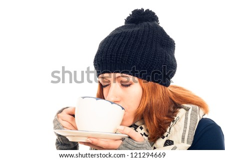 Close up of young woman in winter clothes enjoying hot drink, isolated on white background with copy space. - stock photo