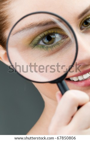 Close-up of young woman looking at camera through magnifying glass