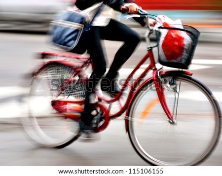 Close up of young woman on bike in blurred motion - stock photo