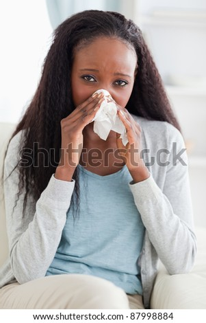 Close up of young woman on couch blowing her nose - stock photo