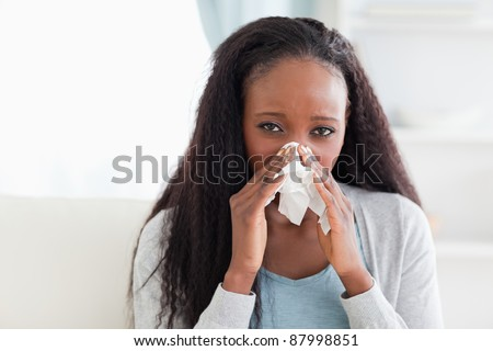 Close up of young woman on sofa blowing her nose - stock photo