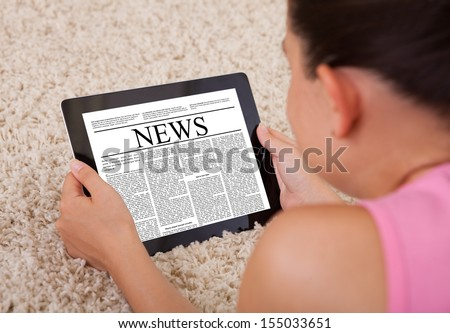Close-up Of Young Woman Reading A News Article On Digital Tablet  - stock photo