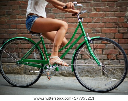 Close-up of young woman riding bicycle against brick wall - stock photo