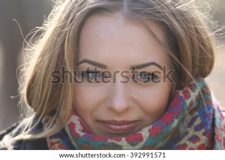 Close Up Of Young Woman's Eyes As She Smiles, Her Hair Blows In The Wind