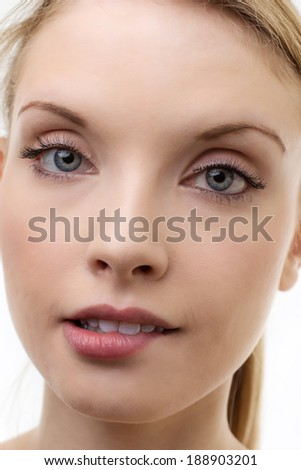close up of young woman's face shot in the studio biting down on her lips