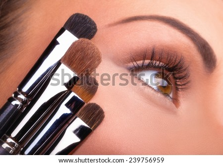 Close up of young woman's face with various brushes for makeup - stock photo