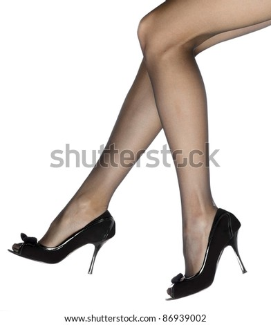 Close-up of young woman's legs in high-heeled black shoes isolated on white