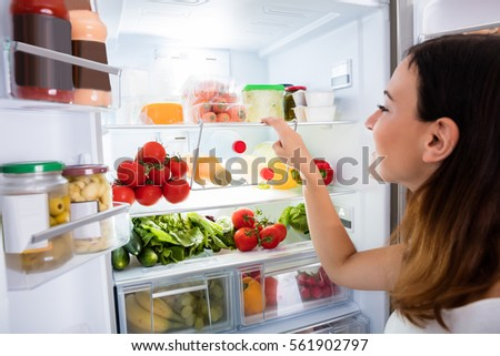 refrigerator in stock. close-up of young woman searching for food in the fridge refrigerator stock r