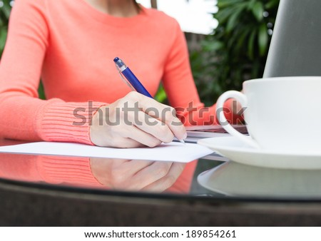 Close up of young woman studying outdoors.  - stock photo