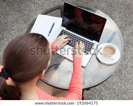 Close up of young woman using laptop outdoors. - stock photo