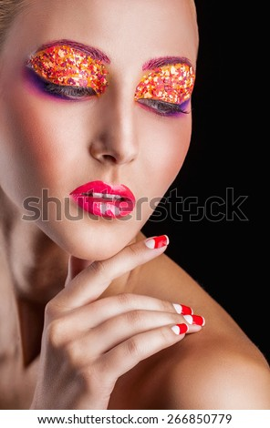 Close-up of young woman with fashion makeup on a dark background