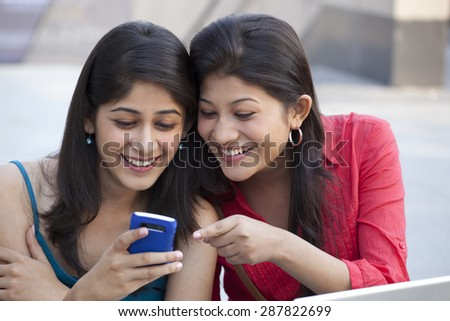 Close-up of young women using cell phone - stock photo