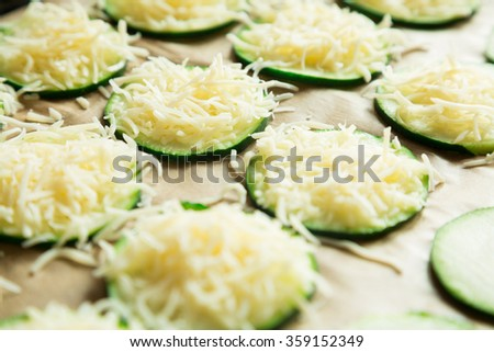 Close up of zucchini slices with grated cheese over brown baking paper ready to bake