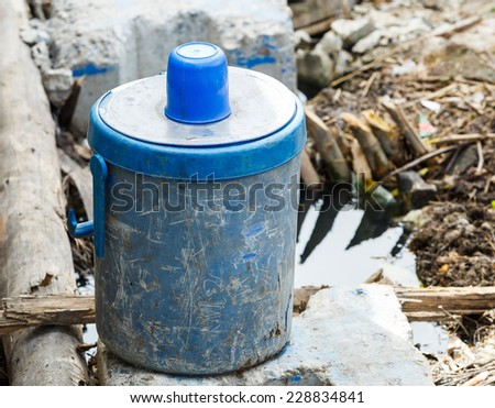 Close up old and dirty ice bucket with plastic cup in construction site - stock photo