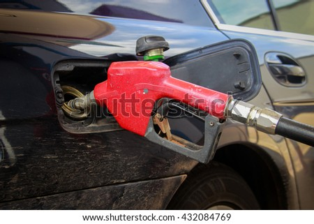 close up old and dirty red nozzle of gas fuel at a gas station pump - stock photo