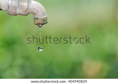 Close up old and grunge faucet and water drop on green blurred background, Water shortage concept. - stock photo
