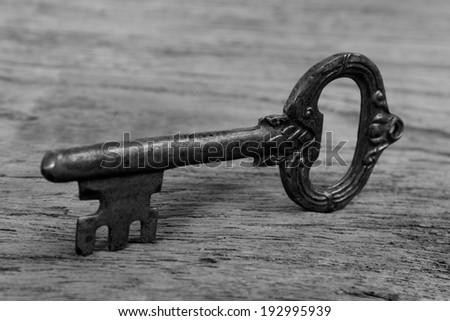 close up old key on wood - stock photo