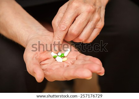 close-up old man's hands with pills - stock photo