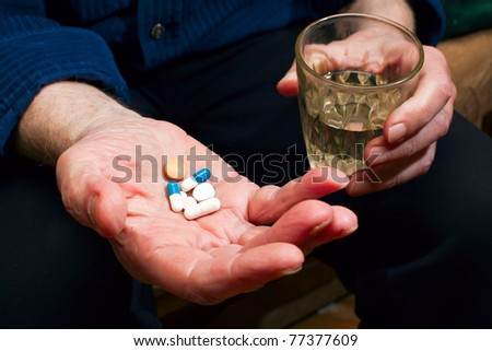 close-up old man's hands with pills and glass of water, he is going to take some medicine