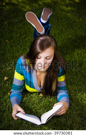 Close up on a Beautiful Girl Laying Down in the Park Reading a Book - stock photo