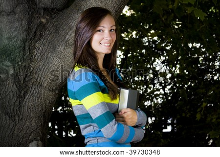 Close up on a Beautiful Teenager with Leaves in the Background - stock photo