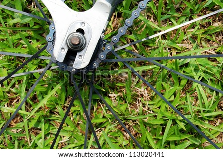 Close-up on a bicycle rear wheel on grass background - stock photo