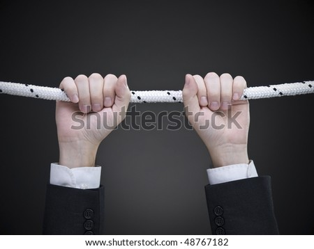 Close up on a businessman's hands hanging on a rope.