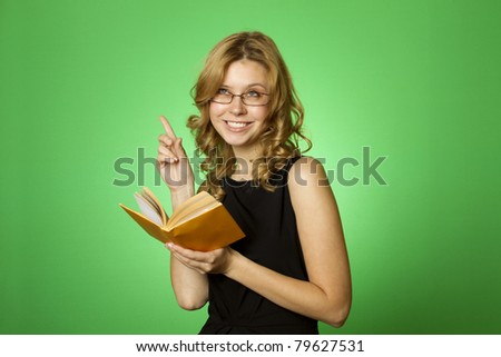 Close-up on a green background attractive girl with glasses and a little yellow book