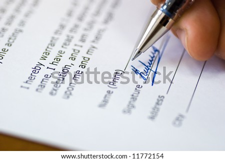 close up on a hand signing a contract - stock photo