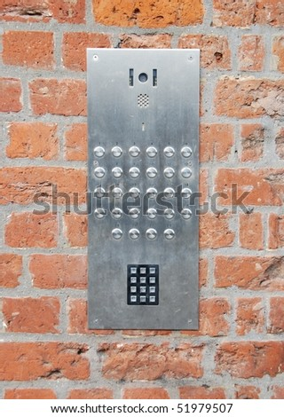 close-up on a intercom doorbell and access code panel on brick wall residential building - stock photo