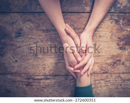 Close up on a man and a woman holding hands at a wooden table - stock photo