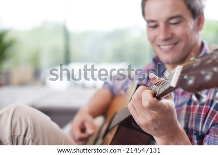 close up on a man playing guitar  focus on one hand - stock photo