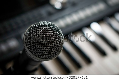 Close up on a microphone during song contest session, keyboard in the background, music studio, selective focusing.