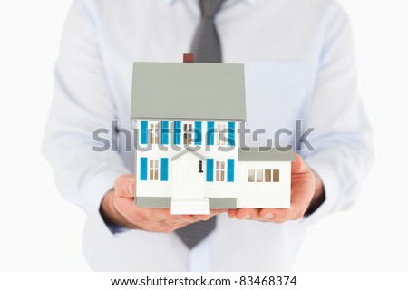 Close up on a miniature house hold by a man - stock photo