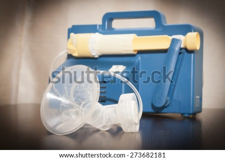 Close up on a old breast pump . A breast pump is a mechanical device that extracts milk from the breasts of a lactating woman. - stock photo