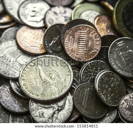 Close up on a pile of American coins US money with main focus on one Dollar coin - stock photo