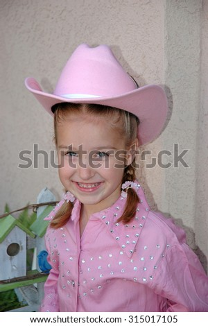 close up on a smiling young caucasian elementary school age child in a pink cowgirl outfit excited to be going to her first square dance - stock photo