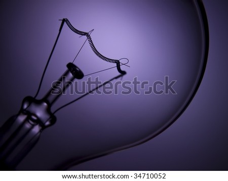 Close up on a transparent light bulb over a purple background.