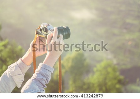 Close up on a woman hand's holding camera. - stock photo