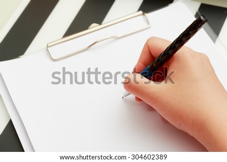 Close up on an asian girl's hand taking note