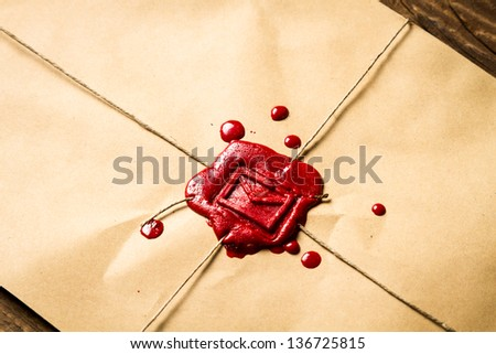 Close-up on an envelope with red sealing wax and old thin rope - stock photo