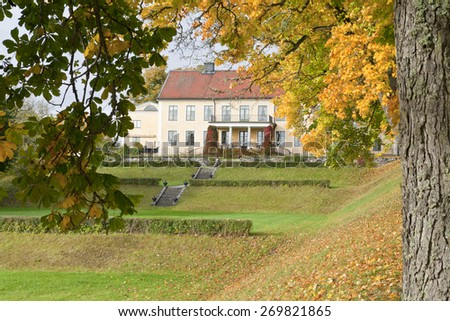 Close up on autumn leaves, chestnut trunk and a yellow building. Garden park in sunshine. - stock photo
